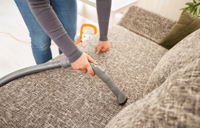person vacuuming sofa