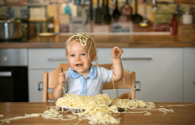 messy toddler covered in pasta